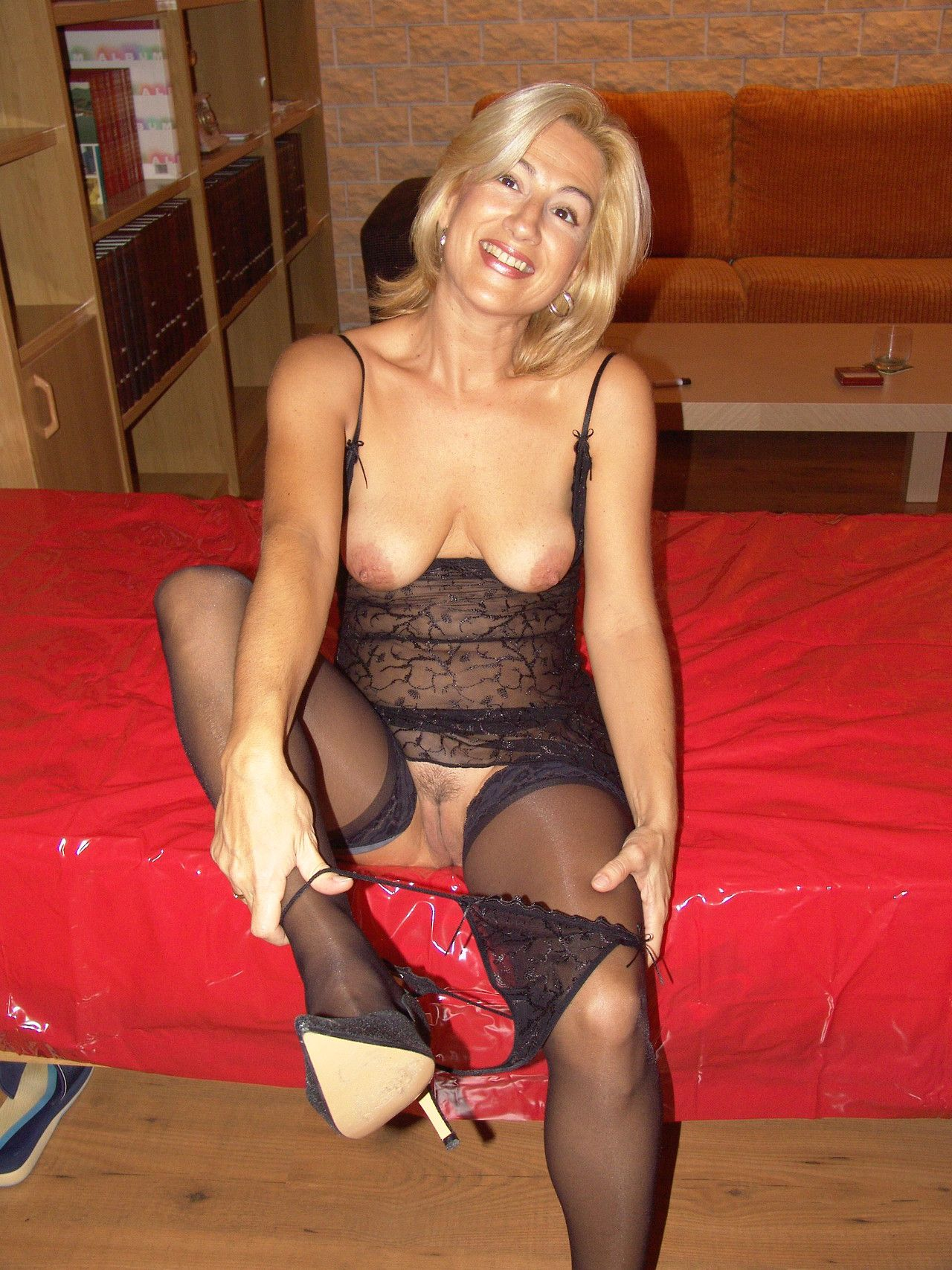 MILF in black lingerie and nylons taking off her lace ...
